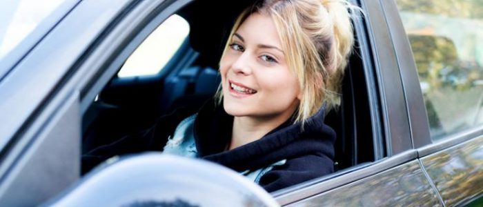 un femme dans la voiture souriante